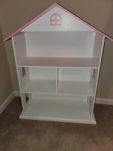 Dollhouse bookshelf with pink roof.