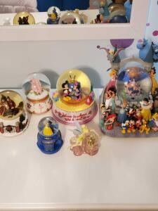 Grouping of four Disney water globes, a ballet water globe, and a caroler's water globe.