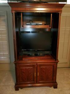 Entertainment armoire with self storing doors and slide out trays.