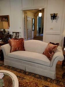 Camelback sofa with rolled arms in tan tweed upholstery.