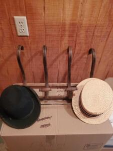 An antique wooden hat rack with a very old bowler hat and a Neiman Marcus, Churchill ldt, straw hat