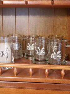 Grouping of glass mugs with pewter emblems.