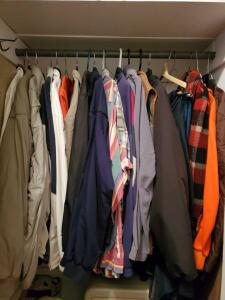 Mens jackets, clothes, and gloves in hall closet.