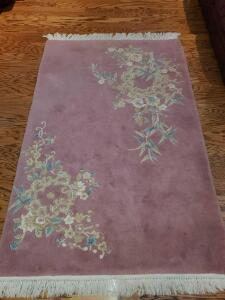 Small wool area rug. Rose color with blue/tan flowers. 72x46""