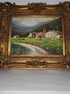 Beautifully framed painting of a home in the mountains.