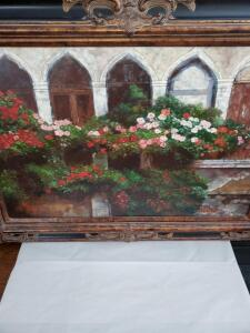 Framed painting of flowers outside along a wall.