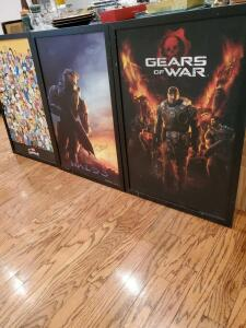 Three framed movie posters. The Simpsons, Halo 3, gears of war.