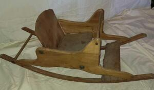 "ANTIQUE CHILD'S ROCKER. WOODEN. SEAT BACK 10"" TALL, ROCKER 14"" TALL, 35"" LONG C 12"" WIDE."