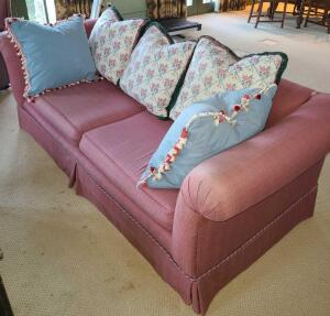 "COUCH MAUVE WITH FLORAL PILLOWS 33"" BACK, 83"" LONG X 40"" DEEP. SOME FADING AND A SMALL TEAR."
