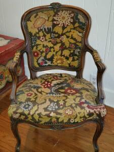 Antique armchair with nailhead trim on needlepoint seat, back, and arms.