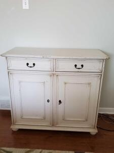 Distressed finish cabinet with two drawers and storage underneath.