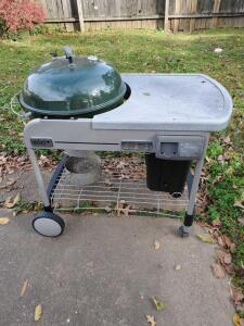 Weber performer charcoal grill with work surface and built in trash can.