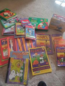 A grouping of peanuts/snoopy items, and a box of vintage childrens books