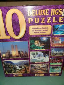 BOX OF 10 DELUXE JIGSAW PUZZLES. INDIVIDUAL PUZZLE BAGS HAVE NEVER BEEN OPENED