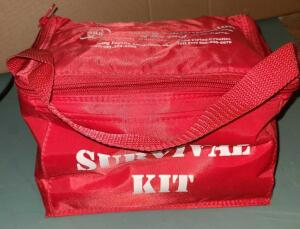 SURVIVAL KIT IN INSULATED BAG. CONTAINS WATER, FOOD RATIONS, BLANKET, FLASHLIGHT, WHISTLE AND