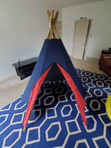 Denim Play tent with wood supports and red bandana door opening.