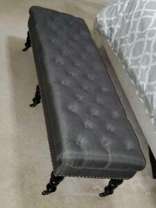 Wonderful gray tweed tufted bench with nailhead trim on casters.