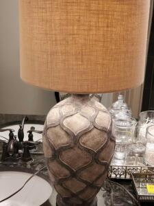 Large pottery vase lamp in colors of gray and stone, with a tan burlap finish shade.