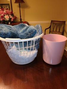 LAUNDRY BASKET WITH TOILET LID COVER AND RUG, TOWELS, AND PINK WASTE CAN.