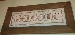 "CROSS STITCHED WELCOME SIGN IN WOODEN FRAME 12"" by 24"""