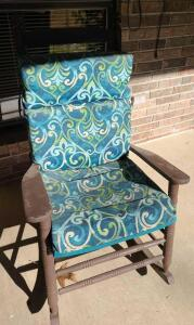 "WICKER ROCKING CHAIR WITH CUSHIONS 46"" TALL X 24"" WIDE X 36"" DEEP."