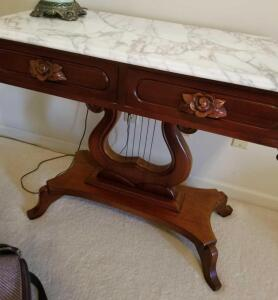 "WOOD AND MARBLE CARVED SIDE TABLE WITH LYRE BASE 31"" TALL, 36"" WIDE, 18.5"" DEEP. HAS TWO DRAWERS."