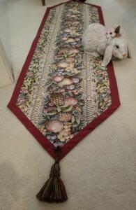 "TASSELLED TABLE RUNNER FRUIT DESIGN 56"" by 17"" AND A CERAMIC RABBIT"