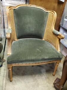 Antique green velvet oversized be chair with cane sides.