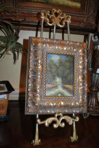 Ornate silver and gold easel with framed oil painting in wood/gold carved frame