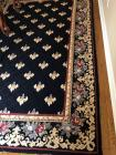 Area rug in colors of black golds and tans