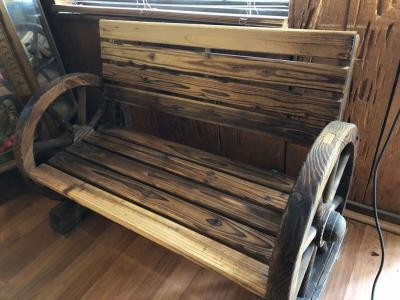 Western style influenced bench with wagon wheel armrest
